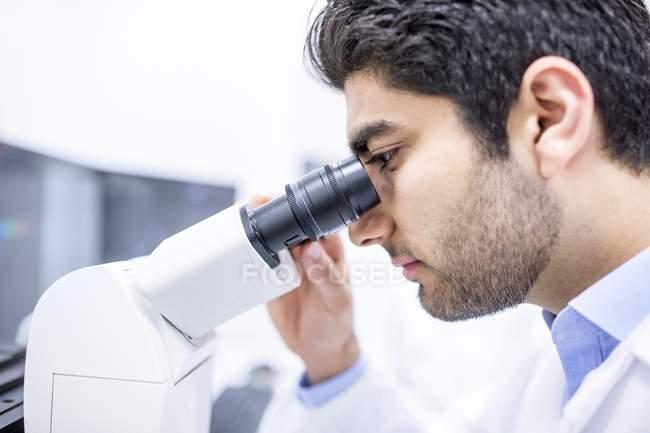 Чоловічий вченого, використовуючи мікроскоп, великим планом. — стокове фото