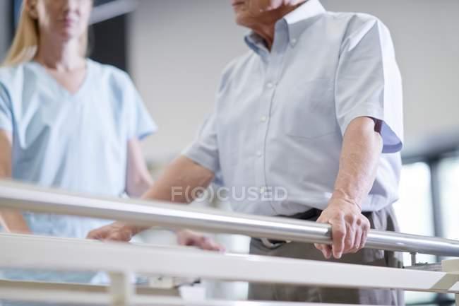 Man using parallel walking bars in hospital. — Stock Photo