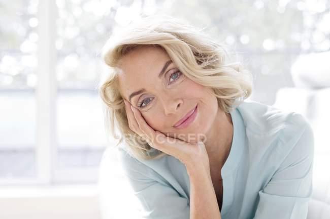 Donna matura che sorride e che guarda a porte chiuse. — Foto stock