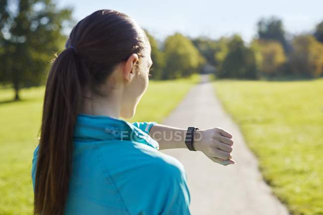 Young woman in sportswear checking watch. — Stock Photo