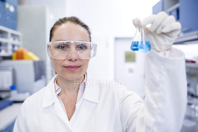 Female laboratory assistant holding chemical flask. — Stock Photo