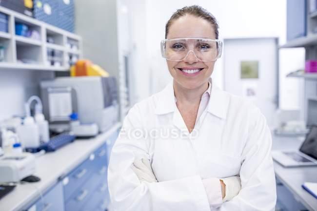 Laborantin in Schutzbrille mit verschränkten Armen. — Stockfoto