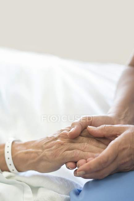 Nurse holding male patient hand in hospital bed. — Stock Photo