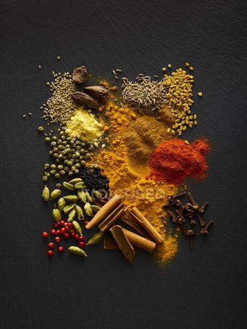 Dried spices on black slate, overhead view. — Stock Photo