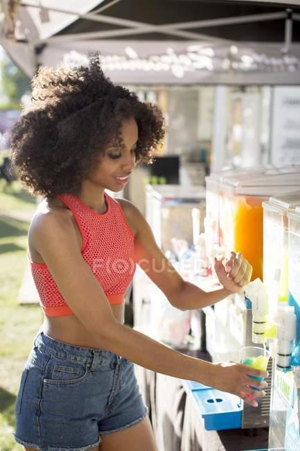 Junge Frau schenkt Getränk auf Jahrmarkt ein. — Stockfoto