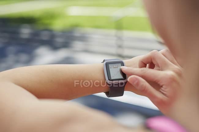 Frau kontrolliert Zeit auf Sport-Smartwatch. — Stockfoto