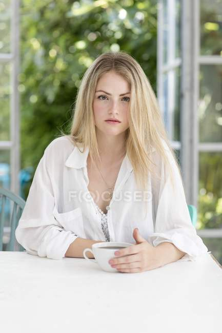 Woman holding coffee cup and looking in camera. — Stock Photo