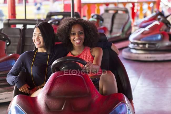Deux femmes s'amusent sur la voiture pare-chocs . — Photo de stock