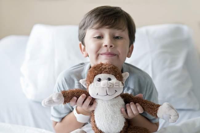 Boy playing with stuffed monkey in hospital bed. — Stock Photo