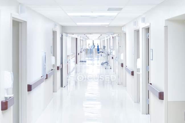 Больничный коридор с размытыми силуэтами врачей — стоковое фото
