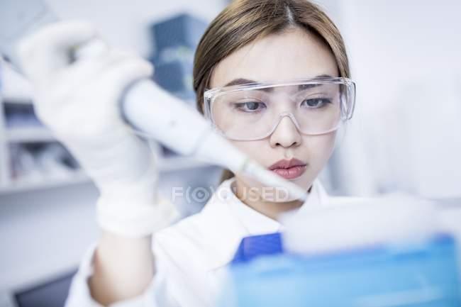 Женщина лаборант с помощью пипетки . — стоковое фото