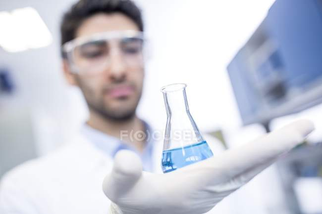 Male laboratory assistant holding chemical flask. — Stock Photo