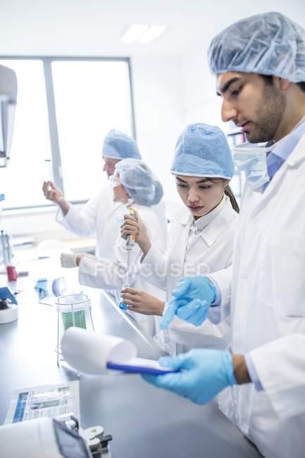 Scientifiques en vêtements de protection travaillant en laboratoire . — Photo de stock