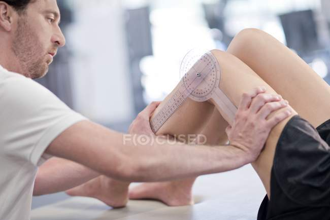 Fisioterapeuta midiendo piernas femeninas . - foto de stock