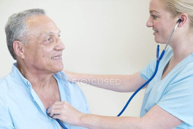 Female doctor examining patient with stethoscope. — Stock Photo