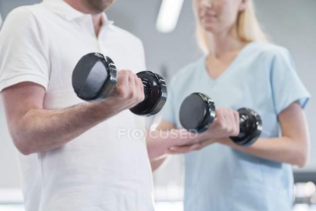 Mujer enfermera ayudar a hombre con pesas. - foto de stock
