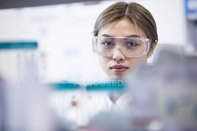 Female laboratory assistant wearing safety goggles. — Stock Photo