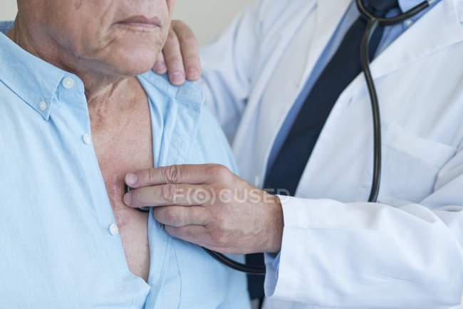 Male doctor examining patient with stethoscope. — Stock Photo