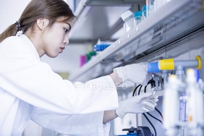 Жіночий лаборант за допомогою крана. — стокове фото