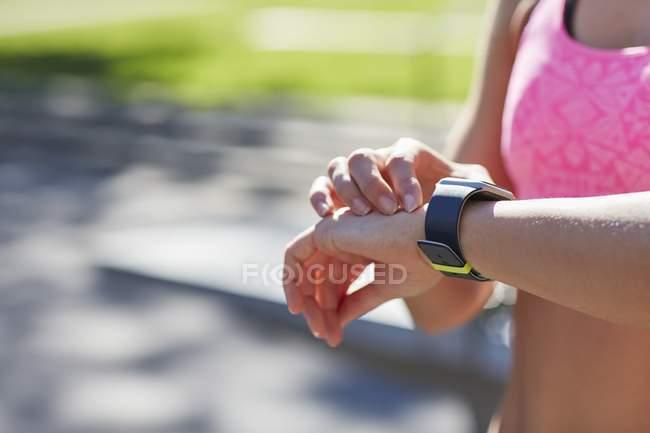 Женщина проверяет время на спортивных умных часах . — стоковое фото