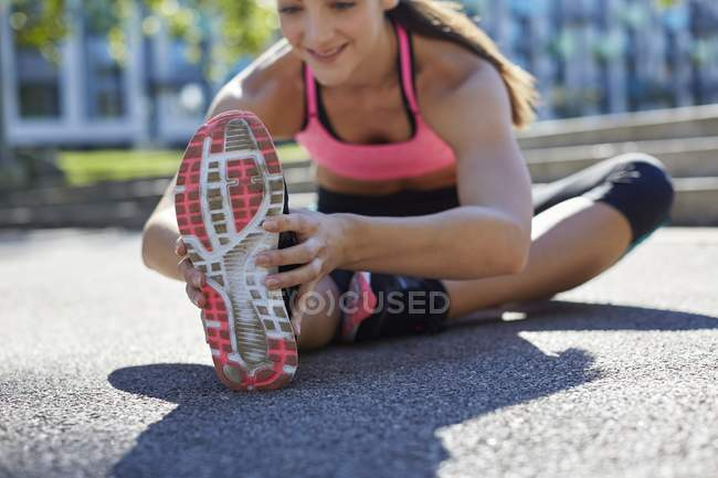 Young woman stretching leg before exercise. — Stock Photo