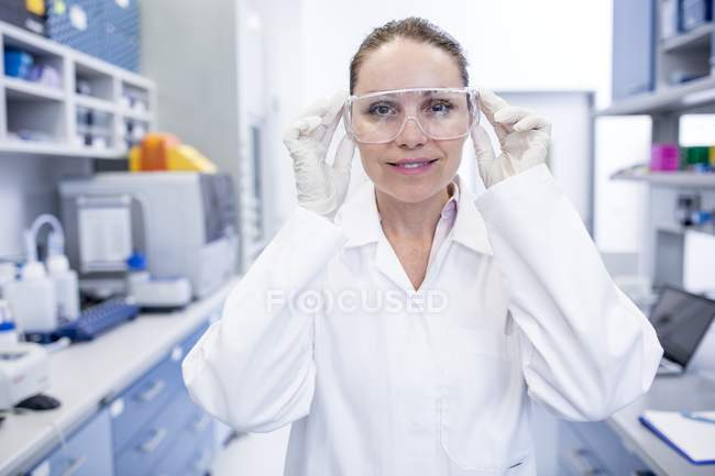 Asistente de laboratorio hembra ajustando gafas de seguridad . - foto de stock