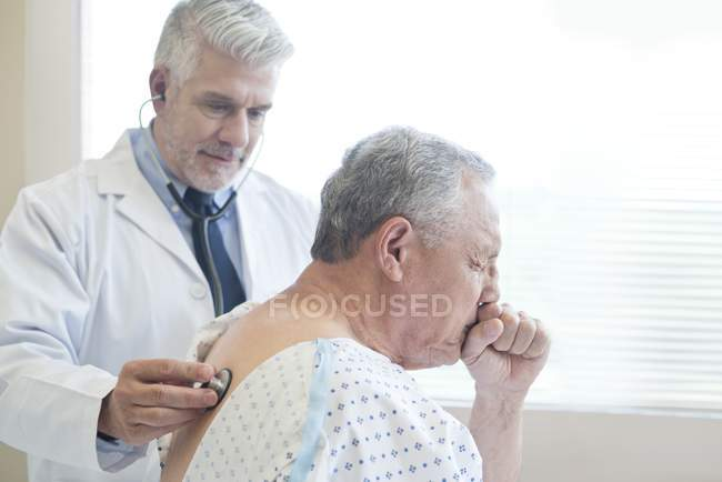 Male doctor examining patient in hospital gown. — Stock Photo