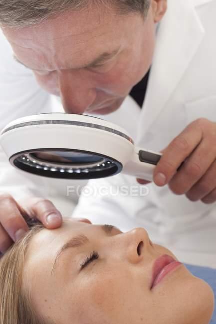 Médico masculino examinando mujer joven usando lámpara de aumento . - foto de stock