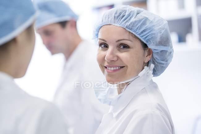 Chirurgin mit OP-Mütze blickt in die Kamera. — Stockfoto