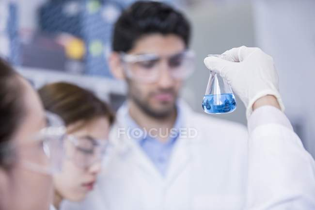 Laboratory assistants looking at chemical flask with blue liquid. — Stock Photo