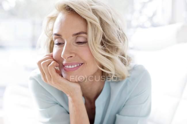 Reife Frau lächelt und schaut weg. — Stockfoto