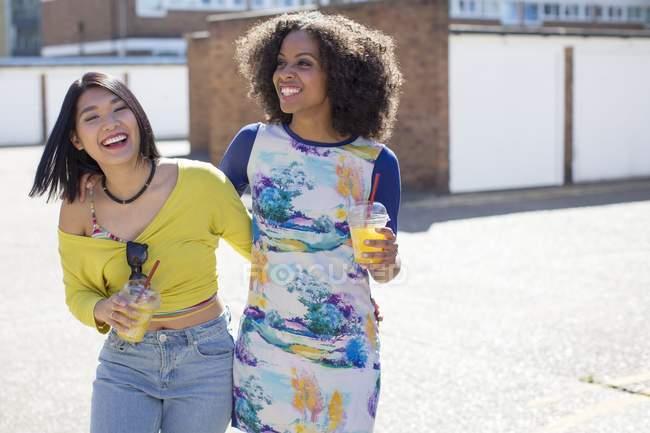 Mujeres sonrientes con bebidas de pie en la calle . - foto de stock