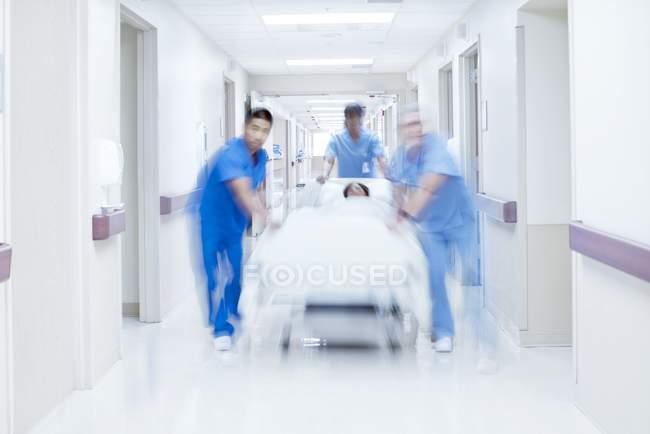 Врачи толкают больничную койку с пациентом по коридору . — стоковое фото