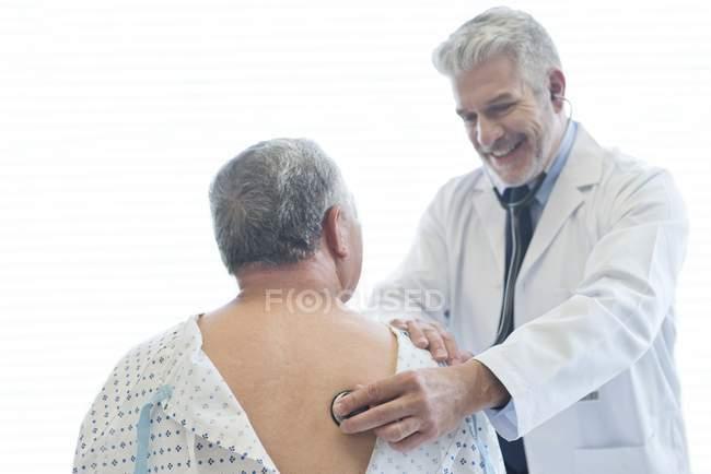 Médico masculino examinando paciente em vestido de hospital . — Fotografia de Stock