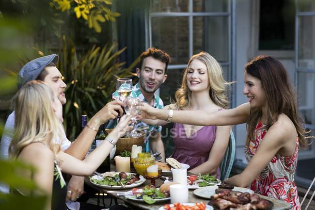 Grupo de amigos brindando con vino en el almuerzo . - foto de stock