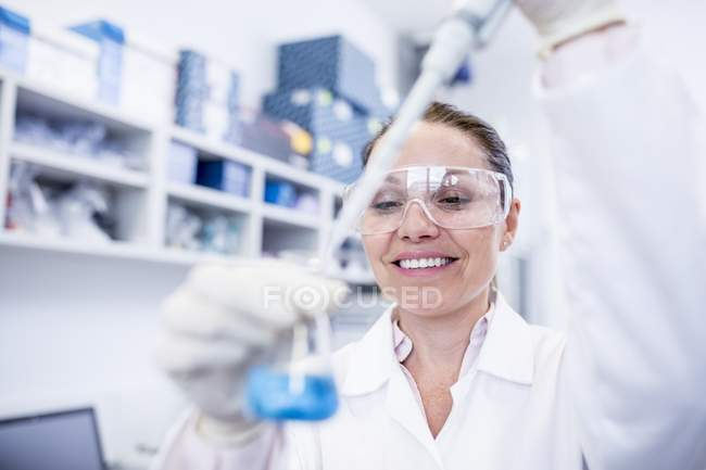 Female laboratory assistant using pipette. — Stock Photo