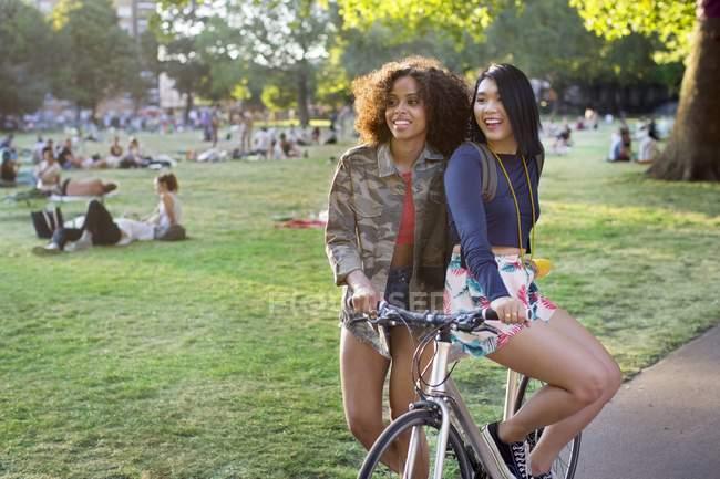 Duas jovens mulheres no parque com bicicleta . — Fotografia de Stock