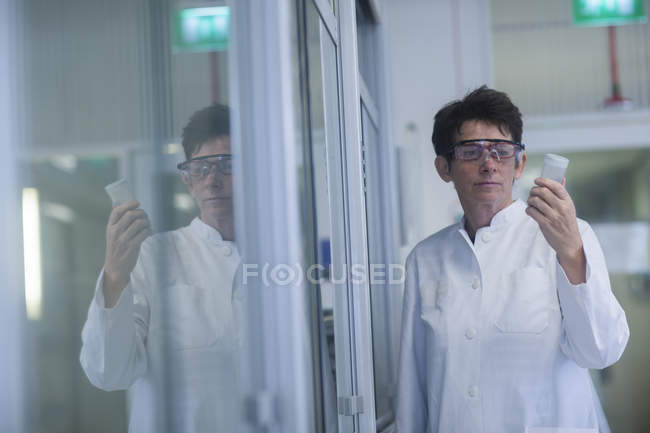 Chemist in protective glasses holding sample in pharmaceutical laboratory. — Stock Photo