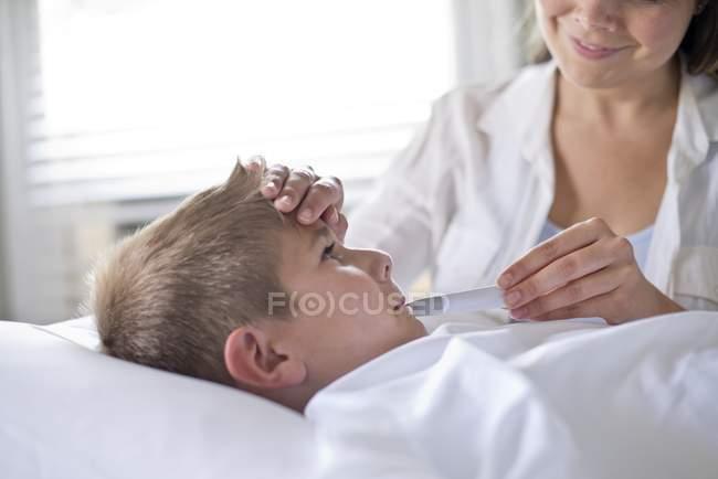 Madre prendendo la temperatura di figlio in letto . — Foto stock