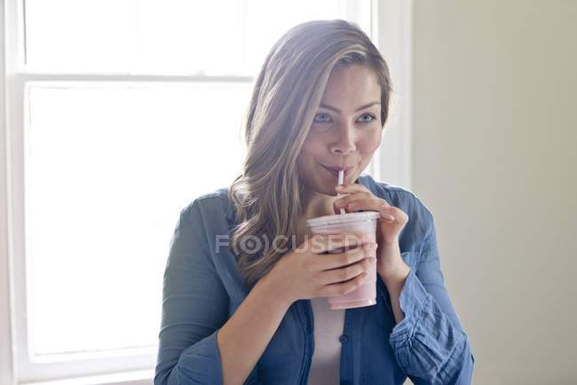 Young woman drinking milkshake with drinking straw — Stock Photo
