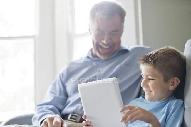 Дед и внук с помощью цифрового планшета и улыбаясь в помещении — стоковое фото
