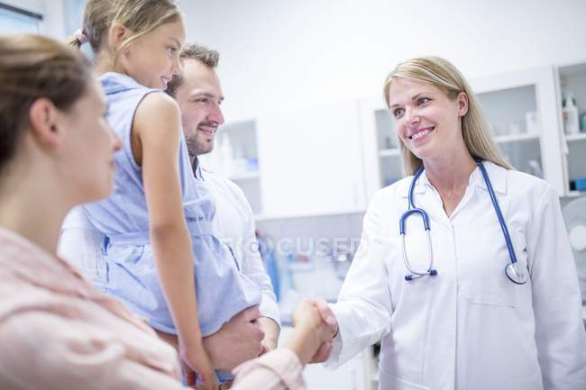 Female doctor talking to family with daughter. — Stock Photo