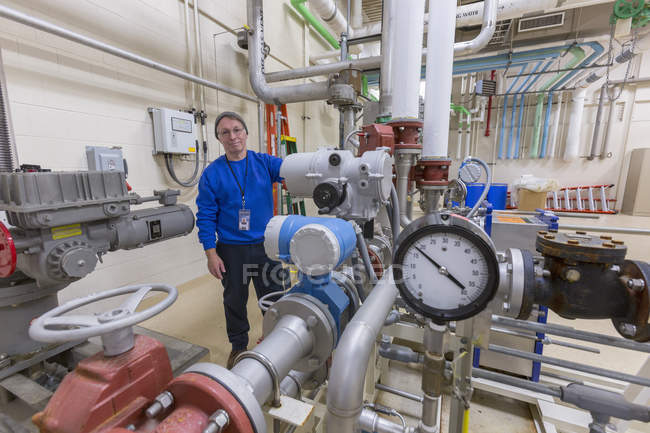 Water treatment engineer inspecting equipment at plant . — Stock Photo