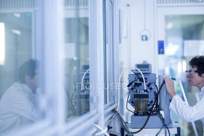 Female chemist setting up equipment in laboratory. — Stock Photo