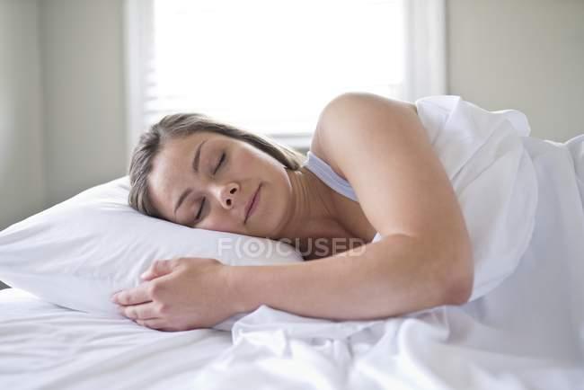 Жінка спати на ліжко в приміщенні. — стокове фото