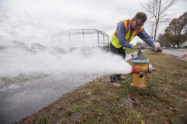 Techniker der Wasserschutzpolizei schaltet Hydranten zum Spülen von Wasserleitungen ab. — Stockfoto