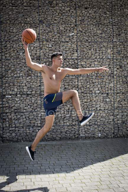 Side view of man jumping with basketball. — Stock Photo