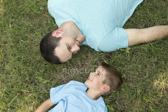 Father and son lying on grass, overhead view. — Stock Photo