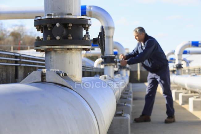 Engineer adjusting water flow control valve. — Stock Photo