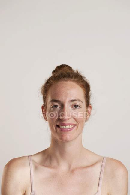 Redhead woman smiling and looking in camera, studio shot. — Stock Photo